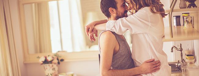 Mann umarmt Frau in der Küche und versucht in Beziehung auf seine Partnerin zuzugehen
