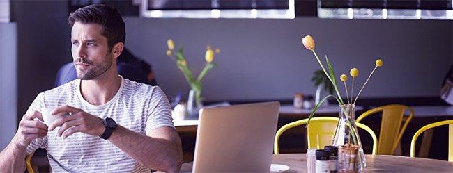 Mann sitzt irritiert im Cafe an seinem Laptop weil er von ElitePartner Abzocke gehört hat