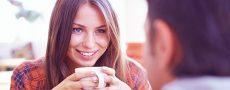 Frau mit Kaffeetasse in der Hand flirtet nach dem online kennenlernen mit Ihrem Date im Café