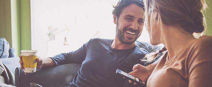 Frau hat Handy in der Hand und sitzt im Café und denkt an ihre Parallelkontakte bei der Partnersuche