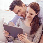 Paar vergibt über Tablet auf Couch Bewertung für ElitePartner, da sie sich hier gefunden haben