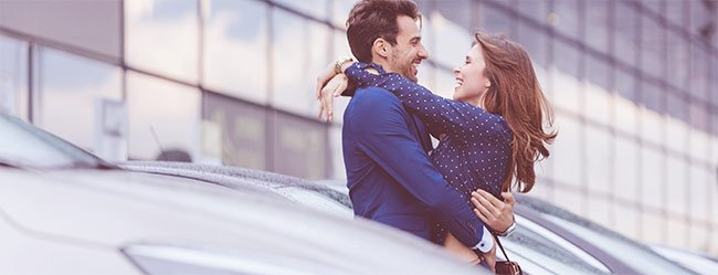 Einer der vier Lebensphasen dargestellt durch Paar dass sich auf einem Parkplatz in die Arme fällt