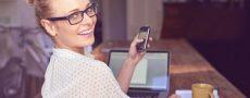 Gründe, warum Fotos bei ElitePartner nicht sichtbar sind werden durch Frau die gerade mit Handy am Laptop über Ihre Schulter schaut dargestellt