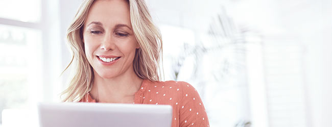 Single-Frau vor Rechner lächelt, das sie die Kontaktgarantie von ElitePartner hat