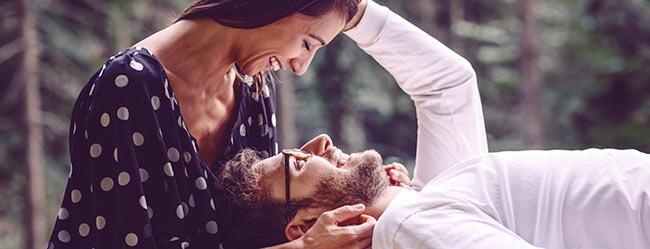 Mann liegt mit Kopf auf Schoß seiner Partnerin und genießt die Vorteile Ihrer Beziehung