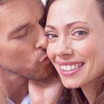 Mann küsst Frau auf die Backe und sie versucht ihn etwas fern zu halten als Symbolbild dafür dass Männer Beziehungsjunkies sind und Frauen den Freiraum brauchen