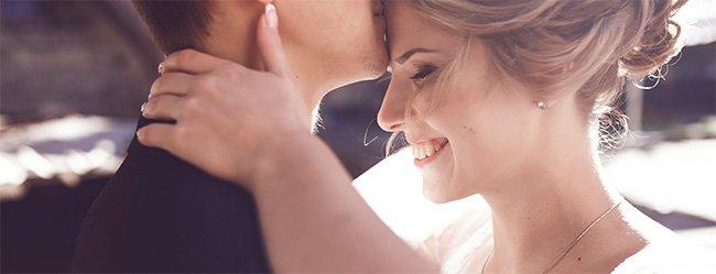 Bräutigam küsst Braut auf die Stirn als Symbolbild für die Vorstellungen beim Heiraten