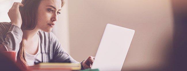 Frau sitzt am Laptop und realisiert, dass sie eifersüchtig auf Ex ist