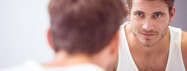 Mann schaut in den Spiegel als Symbol für attraktive Männer