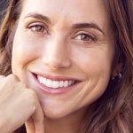 Frau zeigt mit Lächeln ihre Ausstrahlung