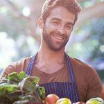 Mann beim Flirten lernen am Gemüsemarkt mit Obstkiste in der Hand