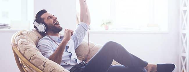 Mann signalisiert Narzissmus, indem er im Sessel sitzt und mit Kopfhörern Musik hört