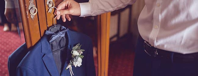"""Mann greift zum Anzug als Symbolbild für die Frage: """"Will er mich heiraten?"""""""