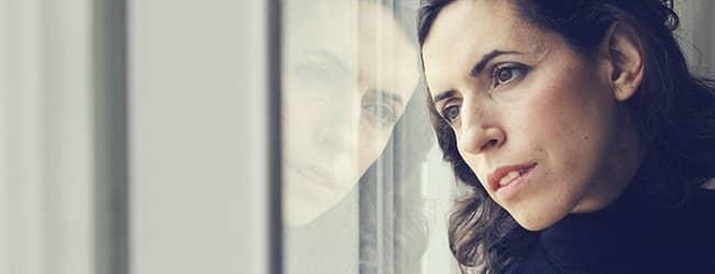 Frau schaut nachdenklich aus dem Fenster und an Zweifel an Beziehung