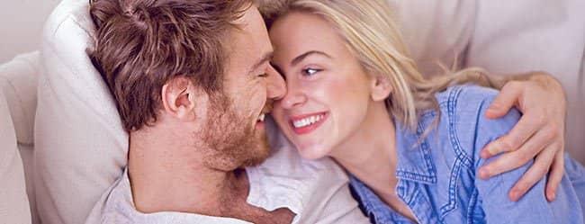 Mann und Frau gemeinsam auf der Couch am in Arm. Glücklich weil sie zusammengezogen sind