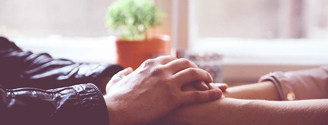 Freundschaft mit dem Ex symbolisch durch zwei aufeinandergelegte Hände von Mann und Frau