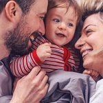 Familie kuschelt zusammen im Bett als Symbolbild dafür wie der Nachwuchs die Beziehung verändert