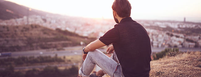 Mann sitzt mit dem Rücken zugewandt auf einem Hang und überlegt Schluss zu machen