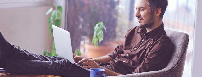 Mann sitzt mit hochgelegten Füßen am Tisch und gestaltet Über mich Text in seinem Profil