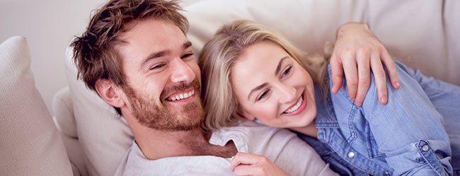 Partnervermittlung hat Frau und Mann, die glücklich auf Couch kuscheln, zusammengebracht