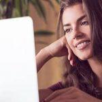 Frau schaut sich Partnerbörse auf ihrem Laptop an