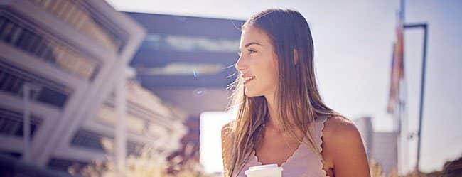 Unnahbare Frau mit Kaffeebecher in der Hand
