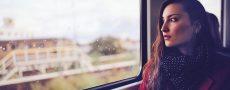 Unglücklich verliebte Frau sitzt im Zug