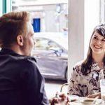 Mann sitzt Frau gegenüber und versucht ihre Körpersprache zu deuten