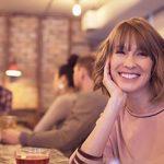 Frau flirtet lächelnd in einer Bar