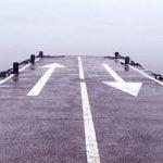 Leere Straße mit Pfeilen in zwei verschiedene Richtung als Symbol dafür, dass sie keine Beziehung will, er aber schon.