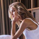 Frau sitzt nachdenklich im Bett und versucht Einsamkeit zu überwinden