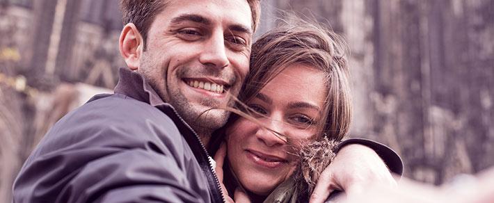 Mann und Frau lächen in Kamera - als Symbol für Beziehungsstatus