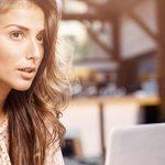 Frau recherchiert am Laptop zu Daten Phishing und Profilübernahme