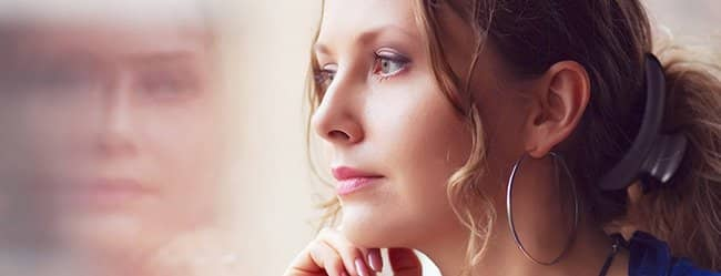 Frau versucht sich zu entlieben und schaut nachdenklich aus dem Fenster