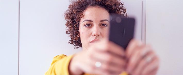 Frau ist schaut gefühlskalt auf ihr Handy