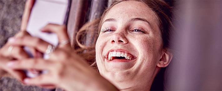 Frau schaut auf Handy und schreibt mit Lückenbüßer