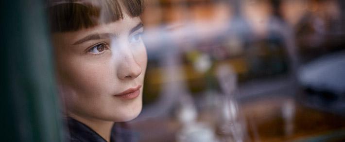 Frau schaut aus dem Fenster - sie hat Angst alleine zu sein