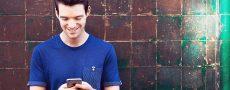 Mann schaut auf sein Smartphone und freut sich über eine Antwort